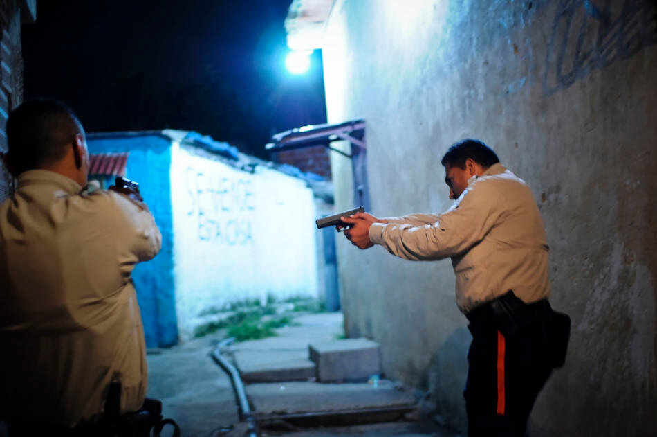Members of a special tactical division of the Sucre police force conduct a late night foot patrol in the Petare area of Caracas, Venezuela.