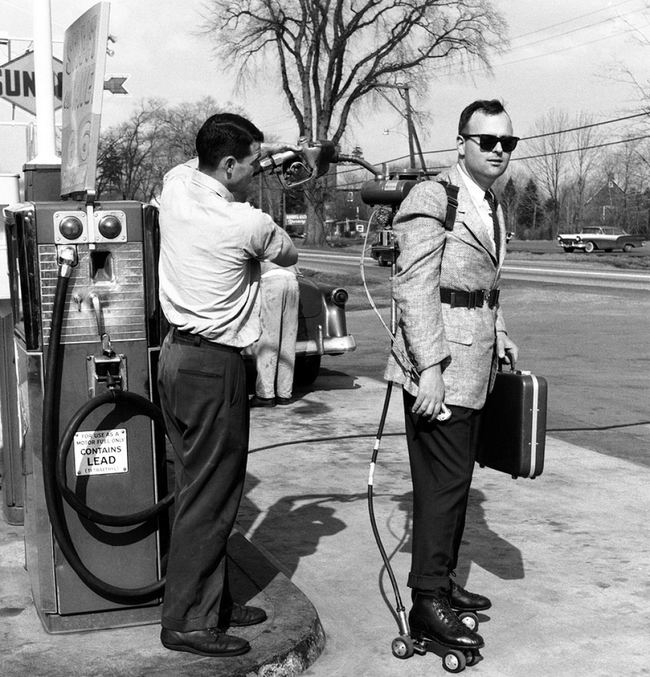 A salesman has his motorized roller skates refueled at a gas station (1961).jpg