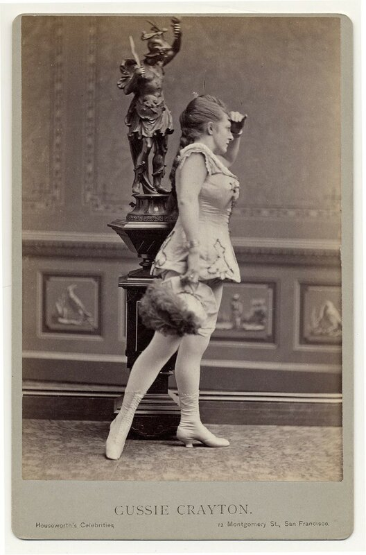 1890. Gussie Crayton.hat with feather, short sleeveless costume with half-calf laced boots.