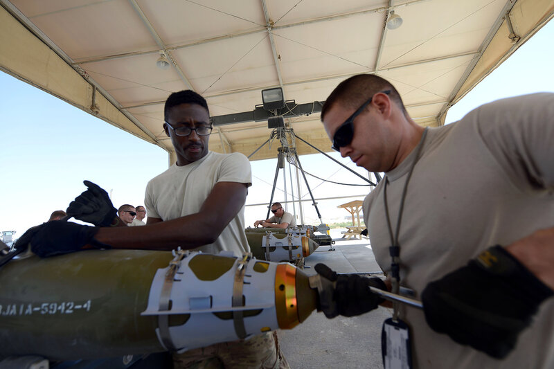 U.S. Air Force Staff Sgt. Terrin Love, a native of Montgomery, Ala., and Senior Airman William Spencer, a native of Kansas City, Mo., work together to tighten the tail end of a GBU-38 bomb at Bagram Airfield, Afghanistan Aug. 14, 2014. The GBU-38 is a vit