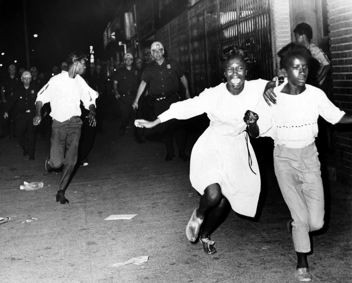 Две перепуганные чернокожие девушки убегают от угрожающих им полицейских во время беспорядков в Бруклине (1964 год)
