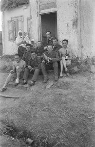 Группа солдат с местной жительницей и двумя детьми перед домом