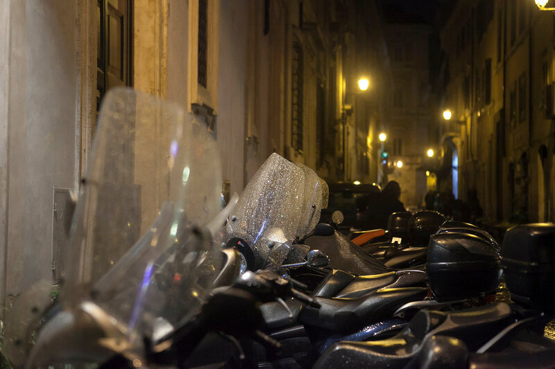 Motorcycles parked against the wall in the light of street lamps