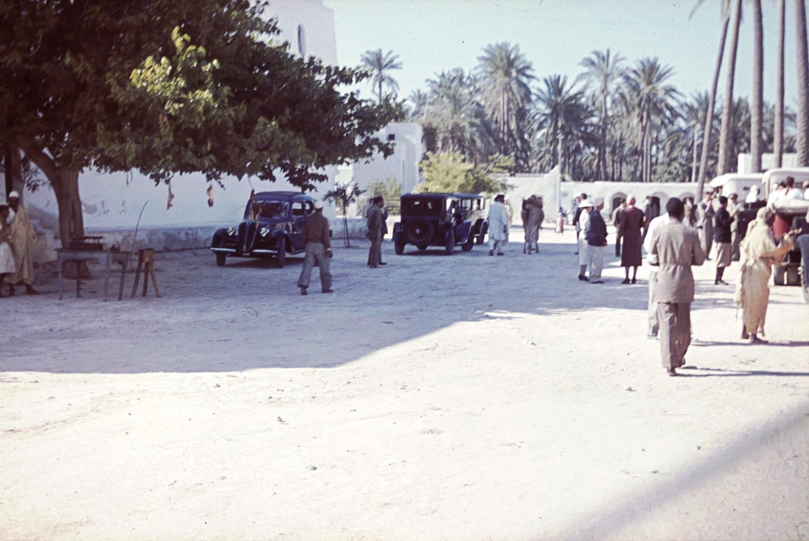 Гадамес. Уличная сцена с местными жителями, автомобилями и пальмами