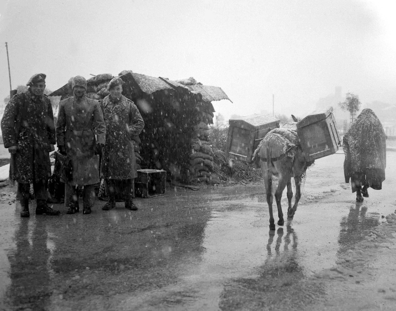 Араб и его ослик проходят блокпост, укомплектованный британскими солдатами и арабским полицейским во время снегопада под Иерусалимом. 22 марта
