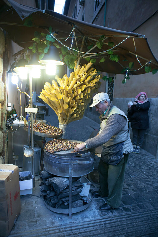 The seller of chestnuts at night in the light of lanterns