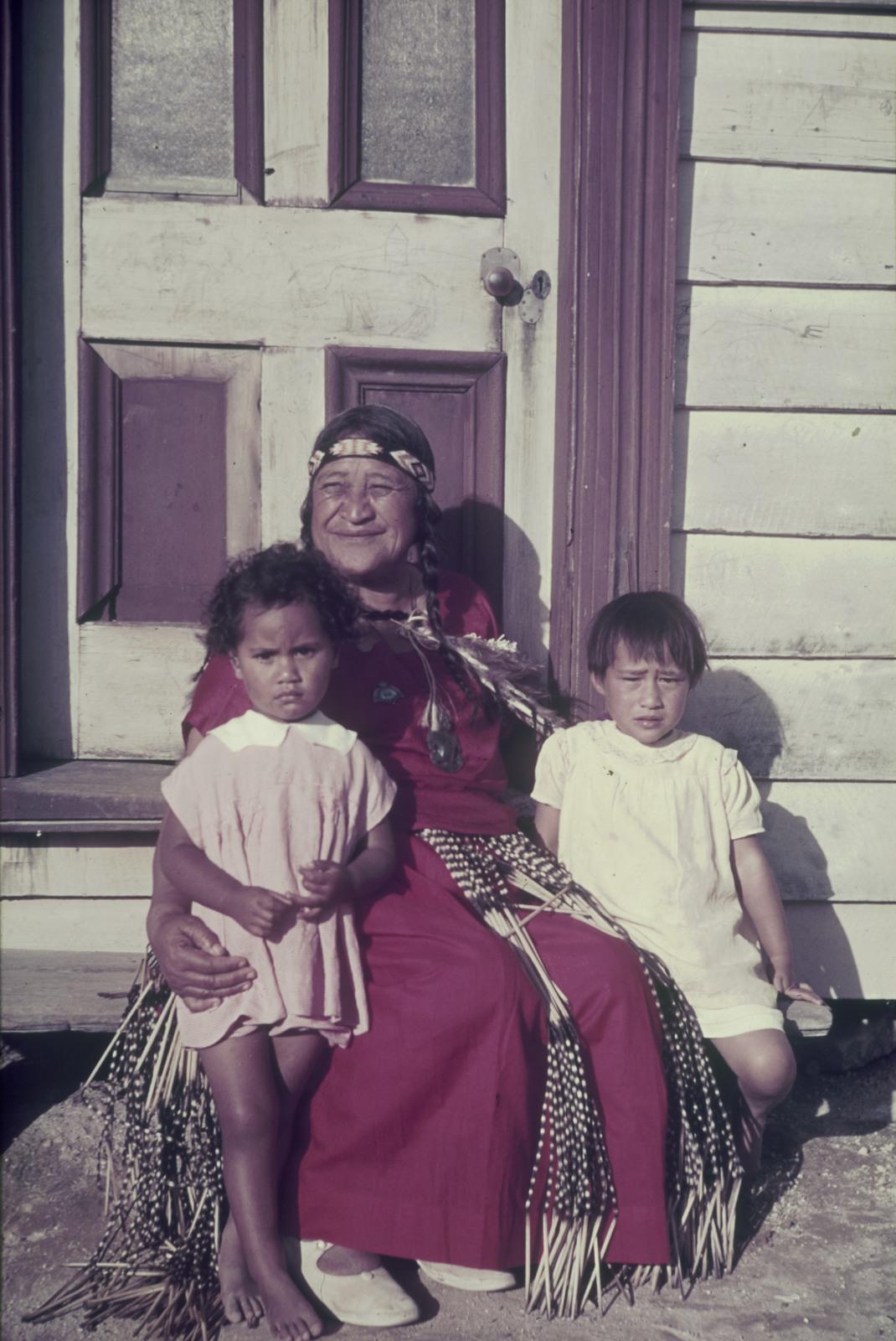 Индейская женщина с двумя маленькими девочками перед входом в деревянный дом