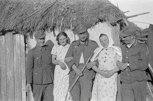 Солдаты и две молодые женщины перед домом