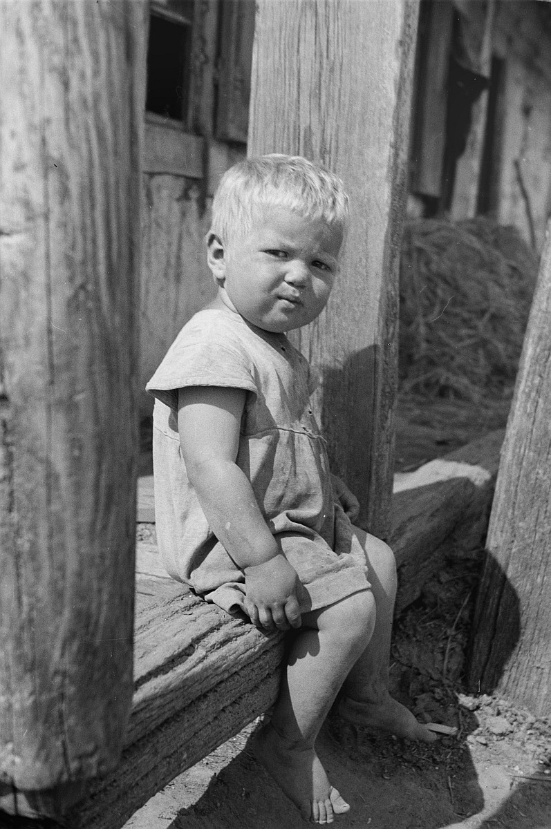 Маленький мальчик на крыльце дома