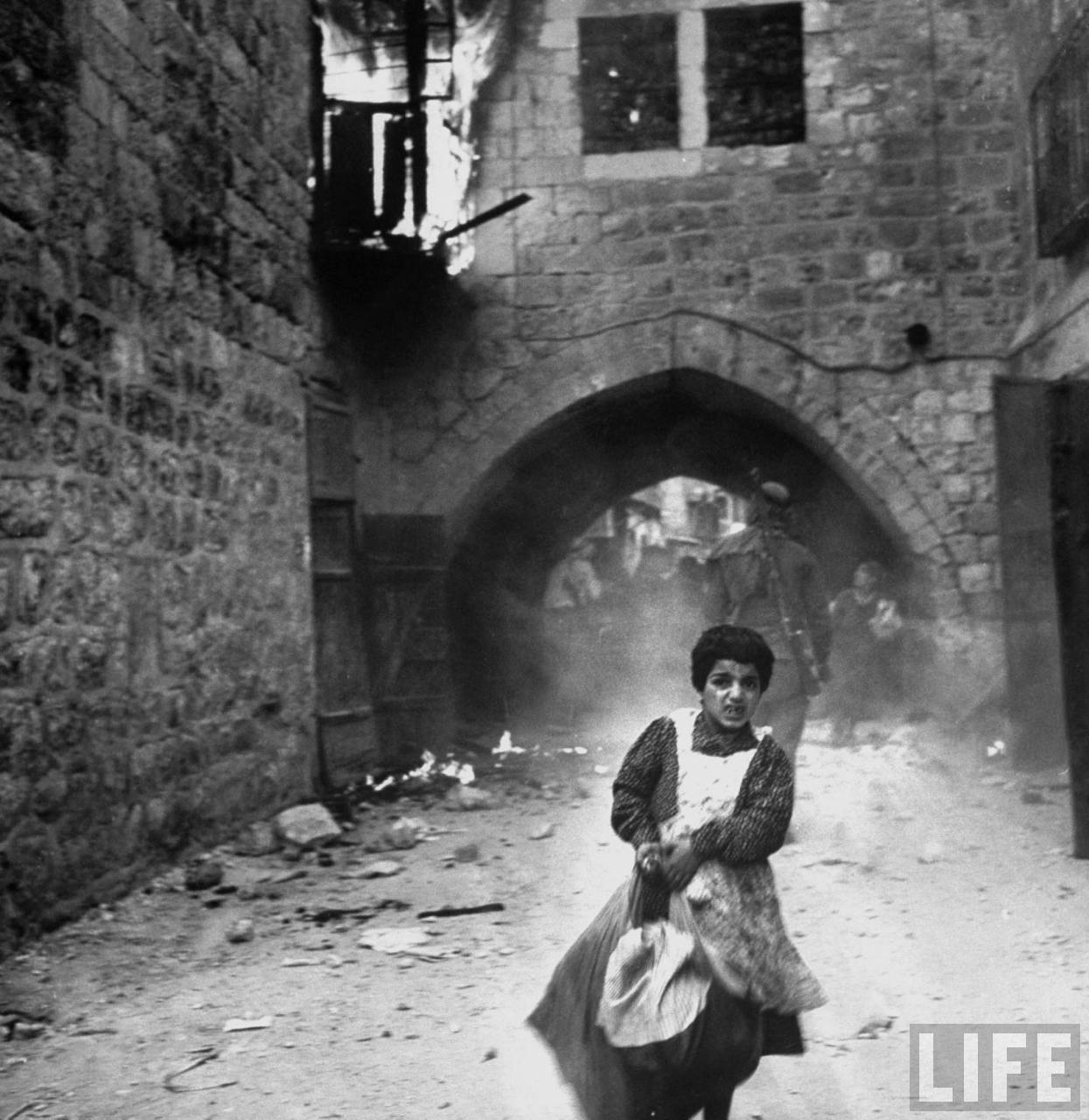 Еврейская девочка Рахиль Леви, 7 лет, бежит по улице от арабов после капитуляции еврейских сил в Иерусалиме.  28 мая