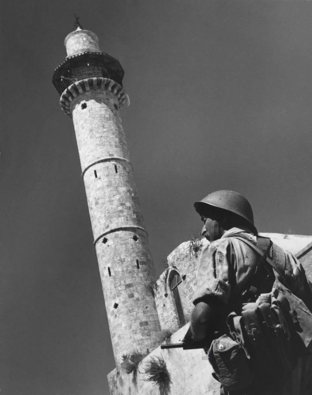 Еврейский солдат на страже перед минаретом в Рамле, после того как город сдался израильским войскам 12 июля