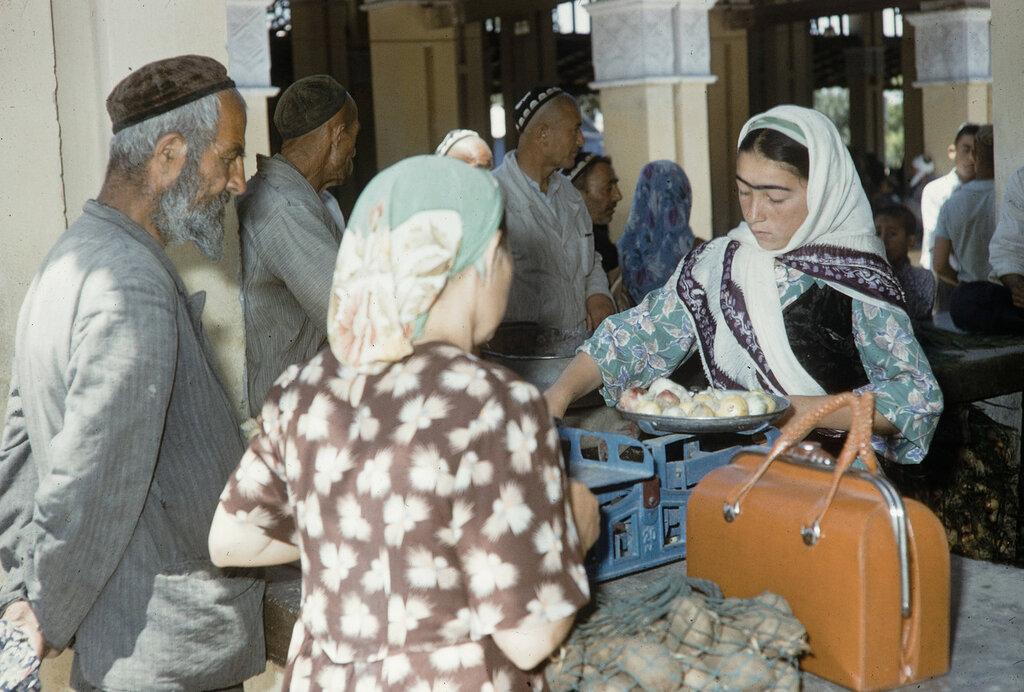 Uzbekistan, merchant weighing produce on scale at market