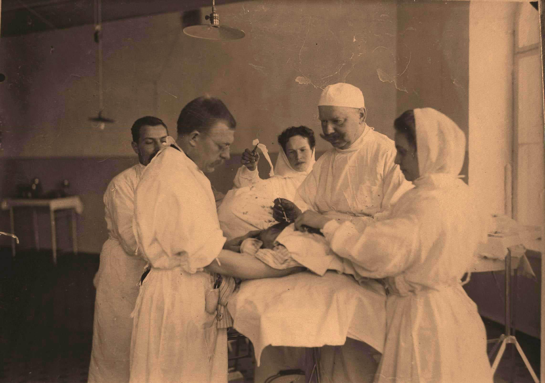 12. Профессор И.Х.Дзирне(справа), доктор Туревич(слева) и сёстры милосердия во время проведения операции раненому в голову