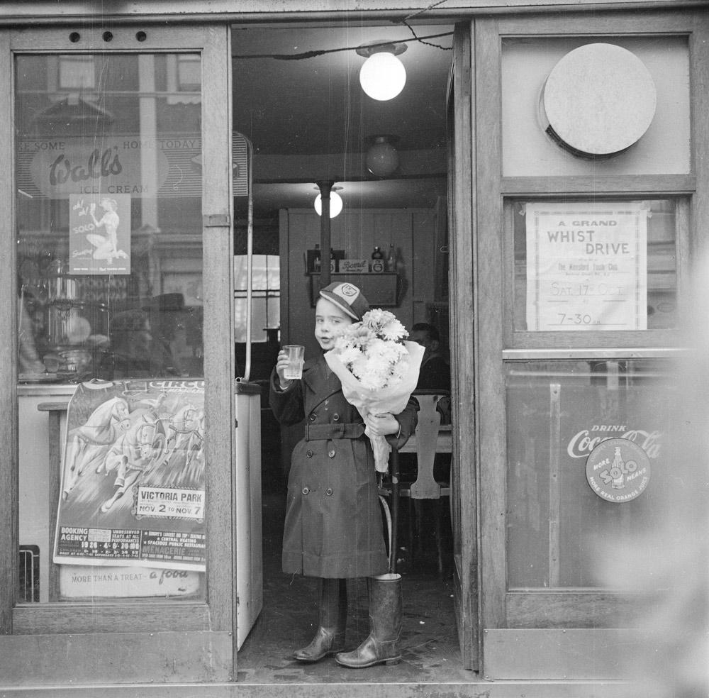 Мальчик со стаканом газировки в дверях магазина