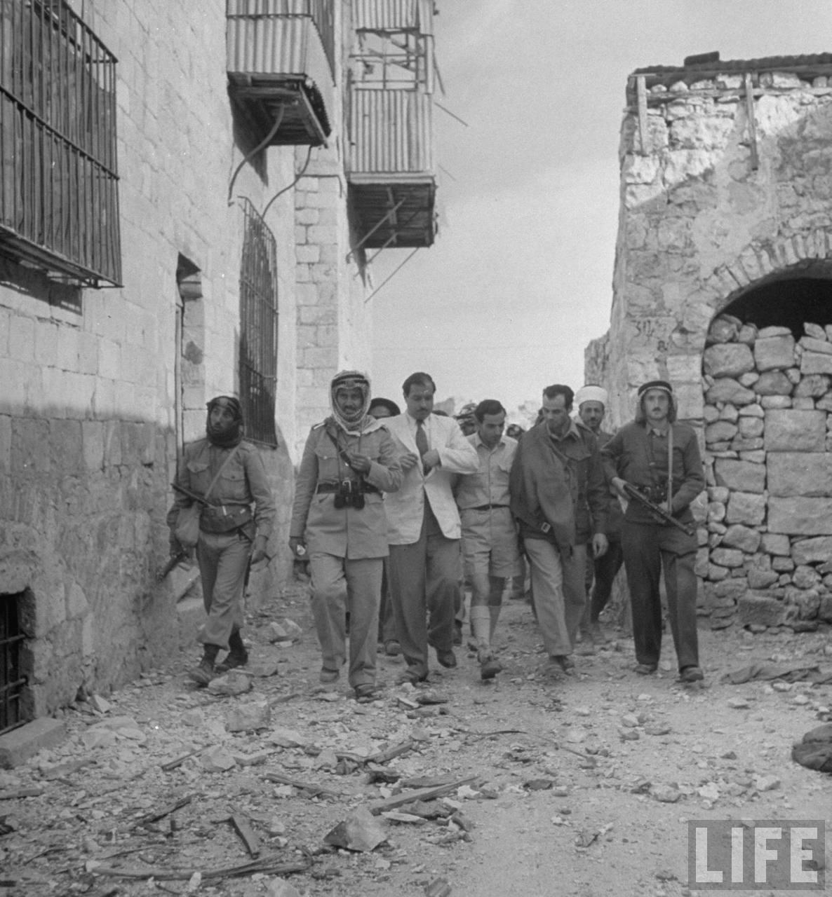 Д-р Мусса Хусейни и лидер сил Хаганы идут с арабскими солдатами после подписания капитуляции Иерусалима
