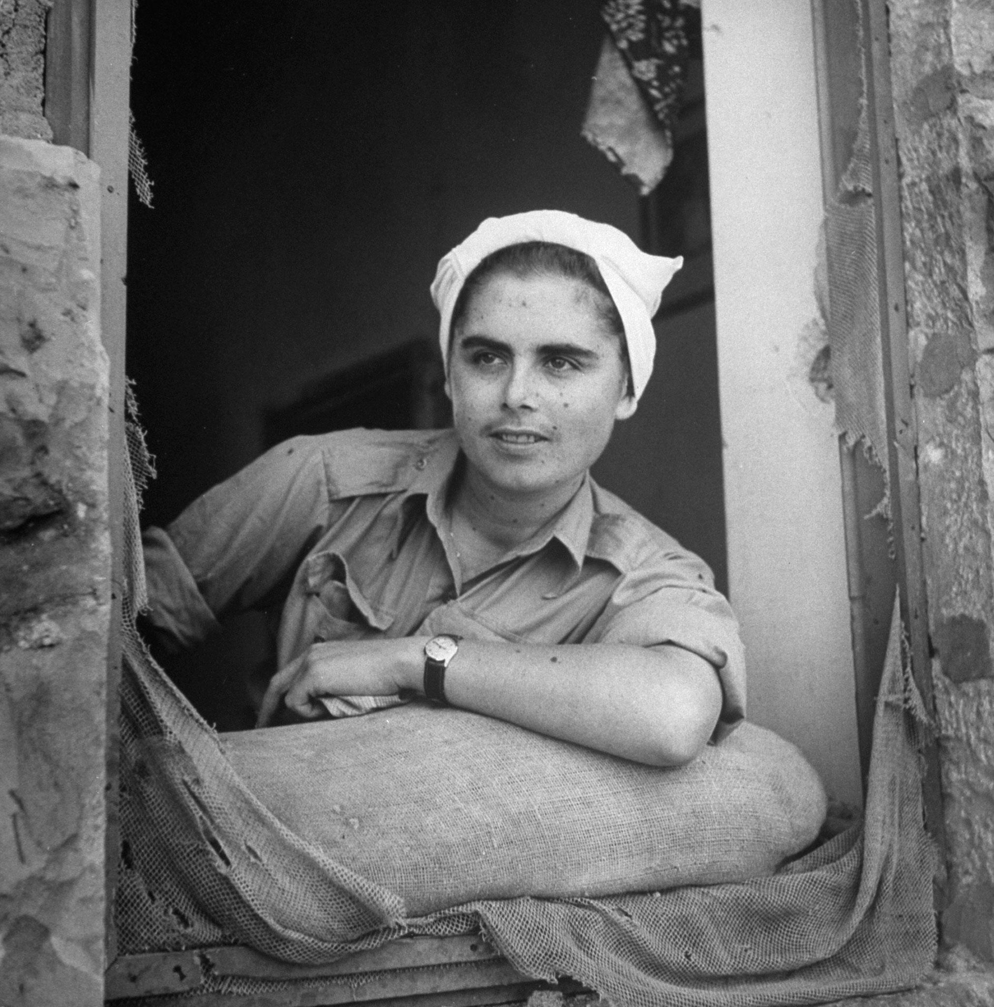 Молодая женщина глядит через  разбитое окно
