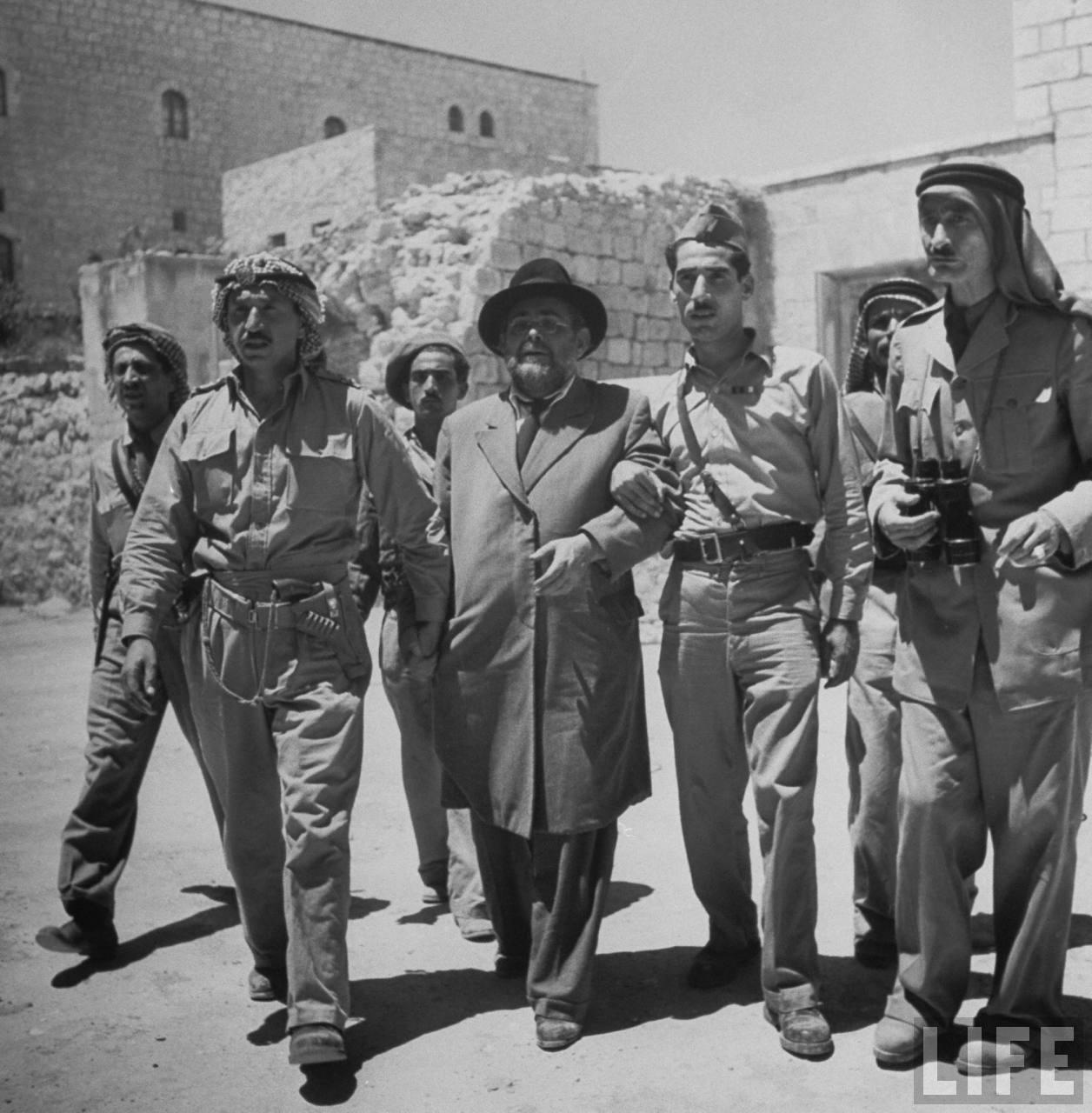 Мэр еврейского квартала «Муктар» Вайнгартен сопровождается арабскими солдатами в штаб-квартиру арабского легиона. Иерусалим. Июнь