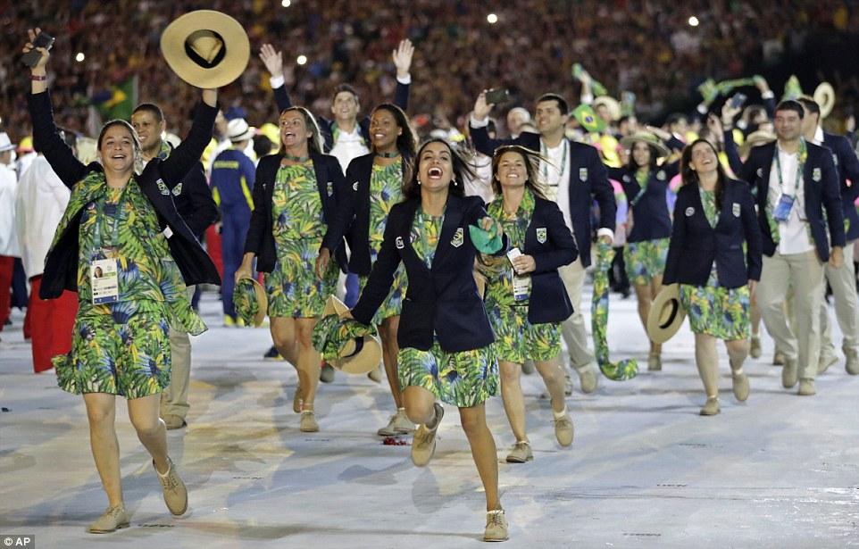 Спереди видно яркие цветастые наряды под темно-синими пиджаками бразильских спортсменов.