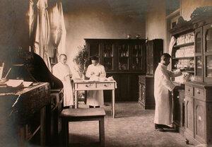 Медицинский персонал за приготовлением лекарств в аптеке больницы.