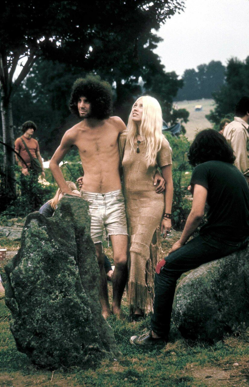 Hippie couple posed together arm in arm