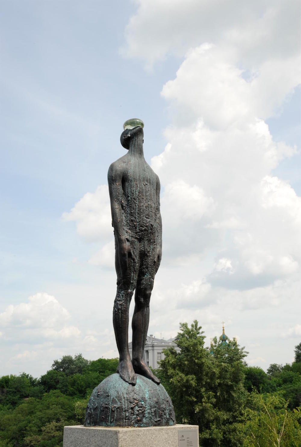 A Giant Glass Raindrop Balances on a Bronze Man's Face in Ukraine