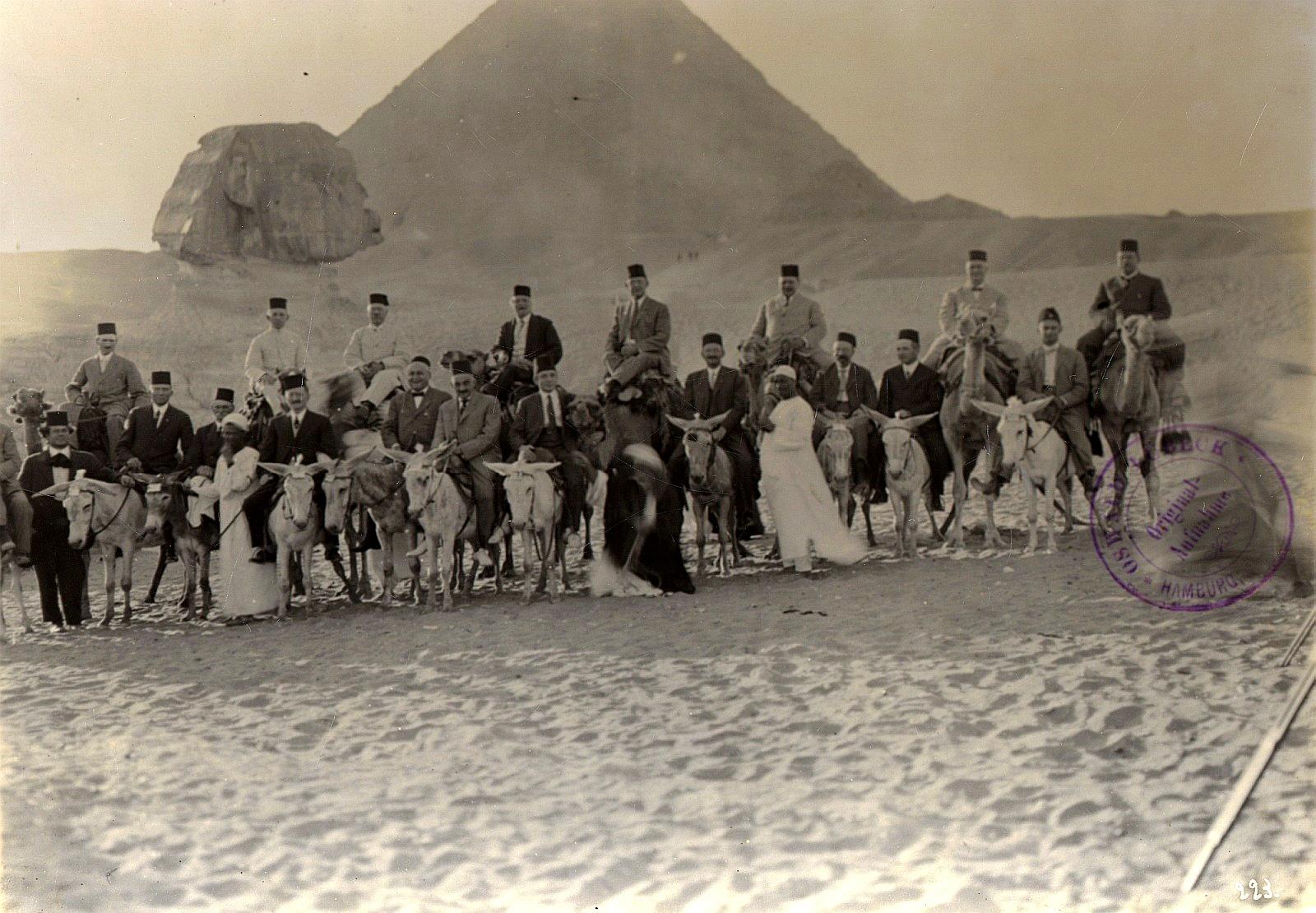 Гиза. Туристическая группа на верблюдах и ослах с гидами перед Сфинксом и пирамидой