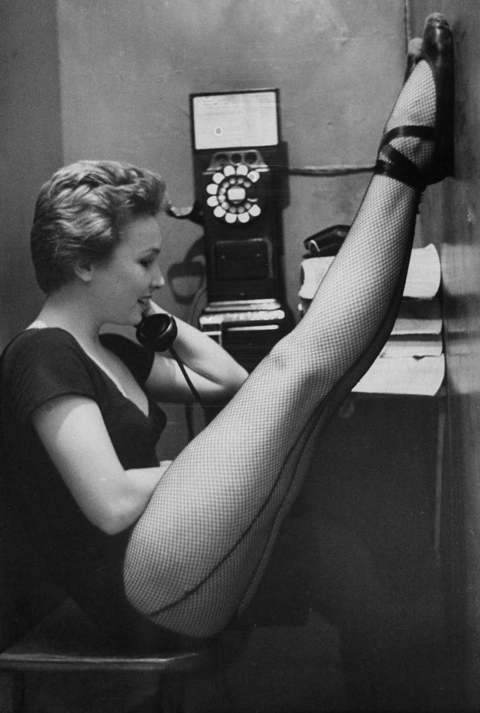 12. Танцовщица Мари Эллен Терри разговаривает по телефону, закинув ноги в колготках на телефонную бу