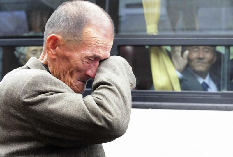 13. Человек из Северной Кореи (справа) машет рукой из автобуса плачущему южнокорейцу после семейной