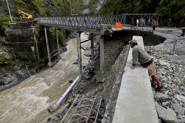 A local resident looks at a bridge damaged at the height of Typhoon Haima in Benguet province, in no
