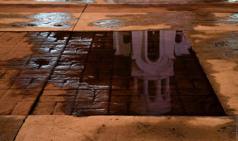 Часовня отражается в луже на каменной мостовой