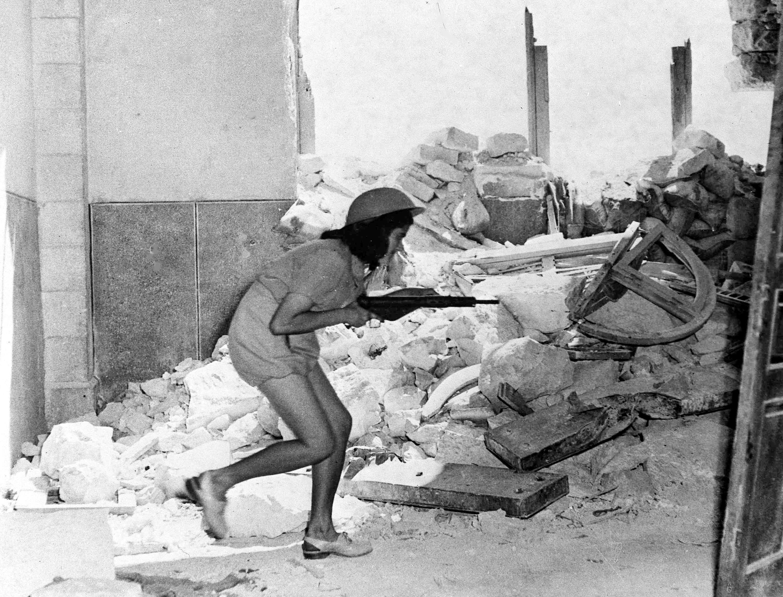 Солдатка пробирается через разрушенные стены в старом городе Иерусалима 20 июля, которые образует линию фронта между арабами внутри и еврейскими силами за стенами