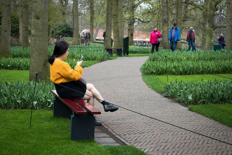 Woman in yellow sweater sitting in the botanical garden of Keukenhof in spring