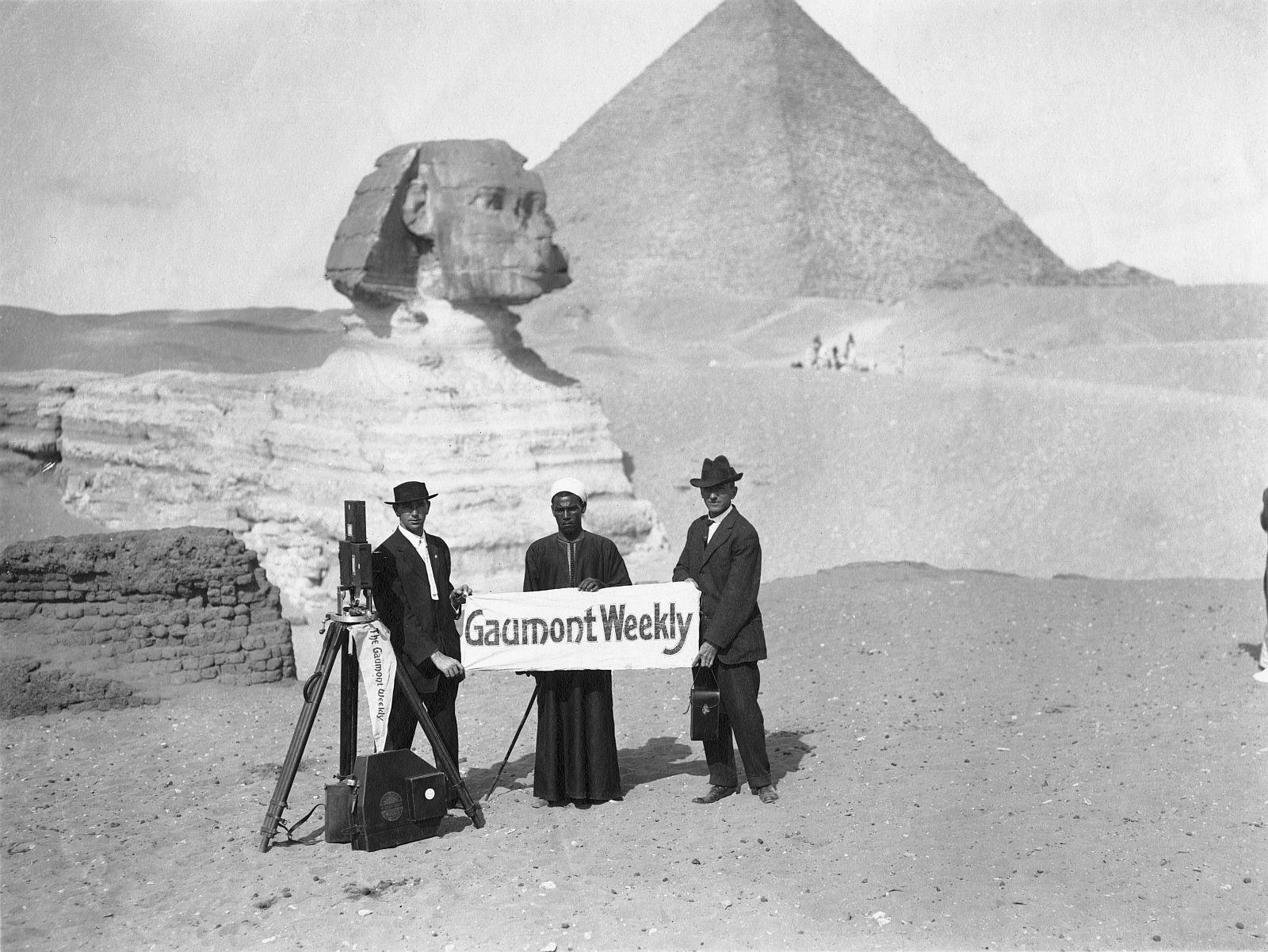 Гиза. Два туриста и местные жители позируют с рекламным баннером «Gaumont Weekly» перед Сфинксом