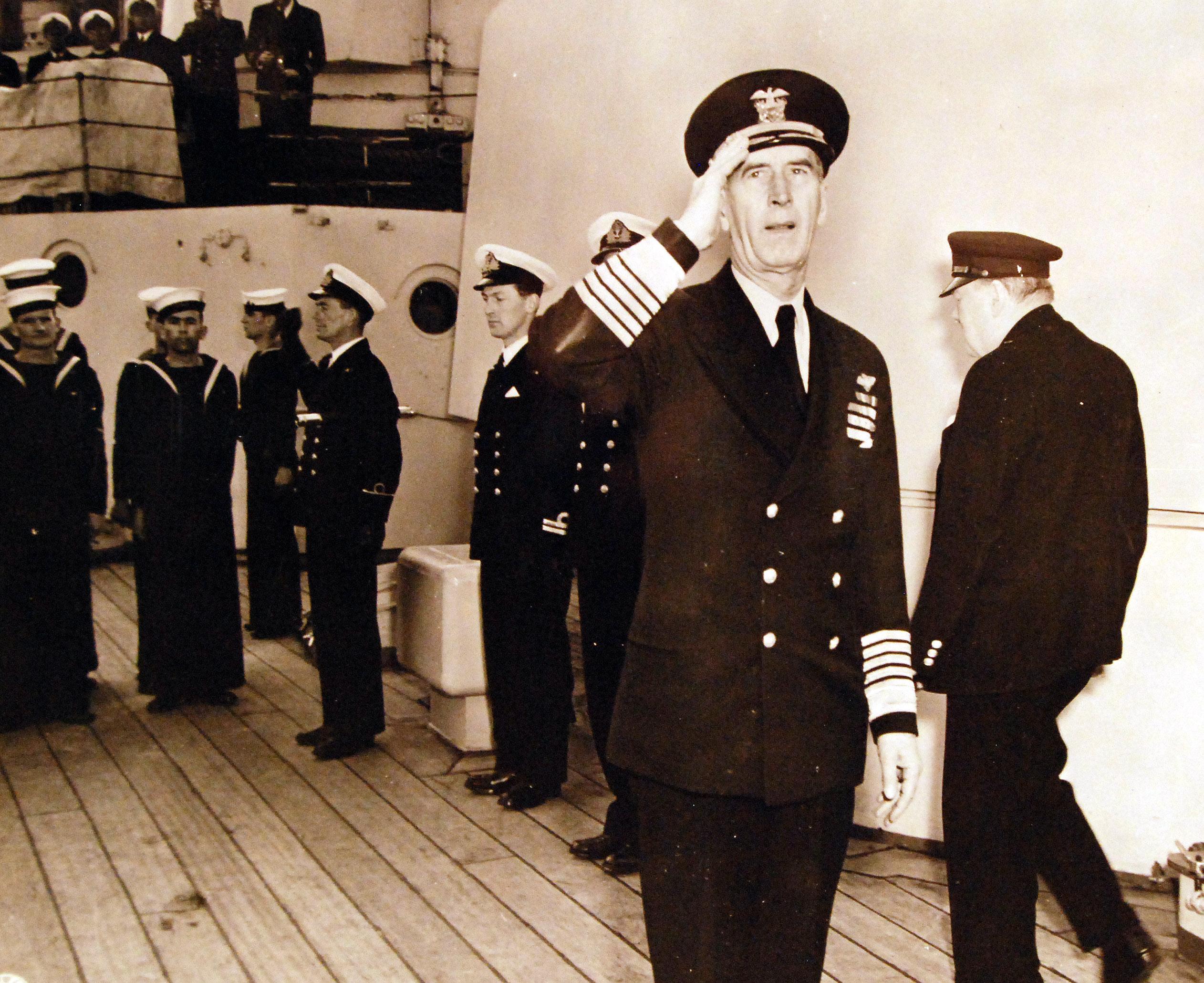 Адмирал флота Эрнест Дж. Кинг салютует во время визита премьер-министра Уинстона С. Черчилля
