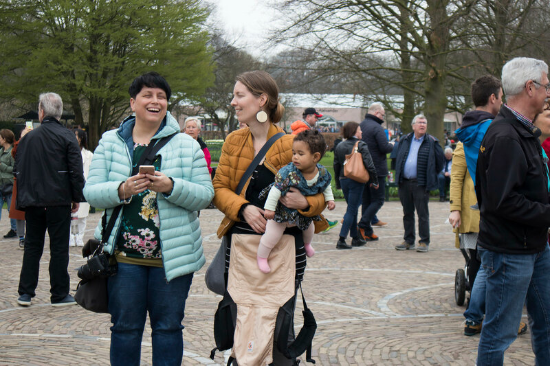 Lisse, Netherlands - April 20, 2018: Woman in yellow sweater sitting in the botanical garden of Keukenhof in spring