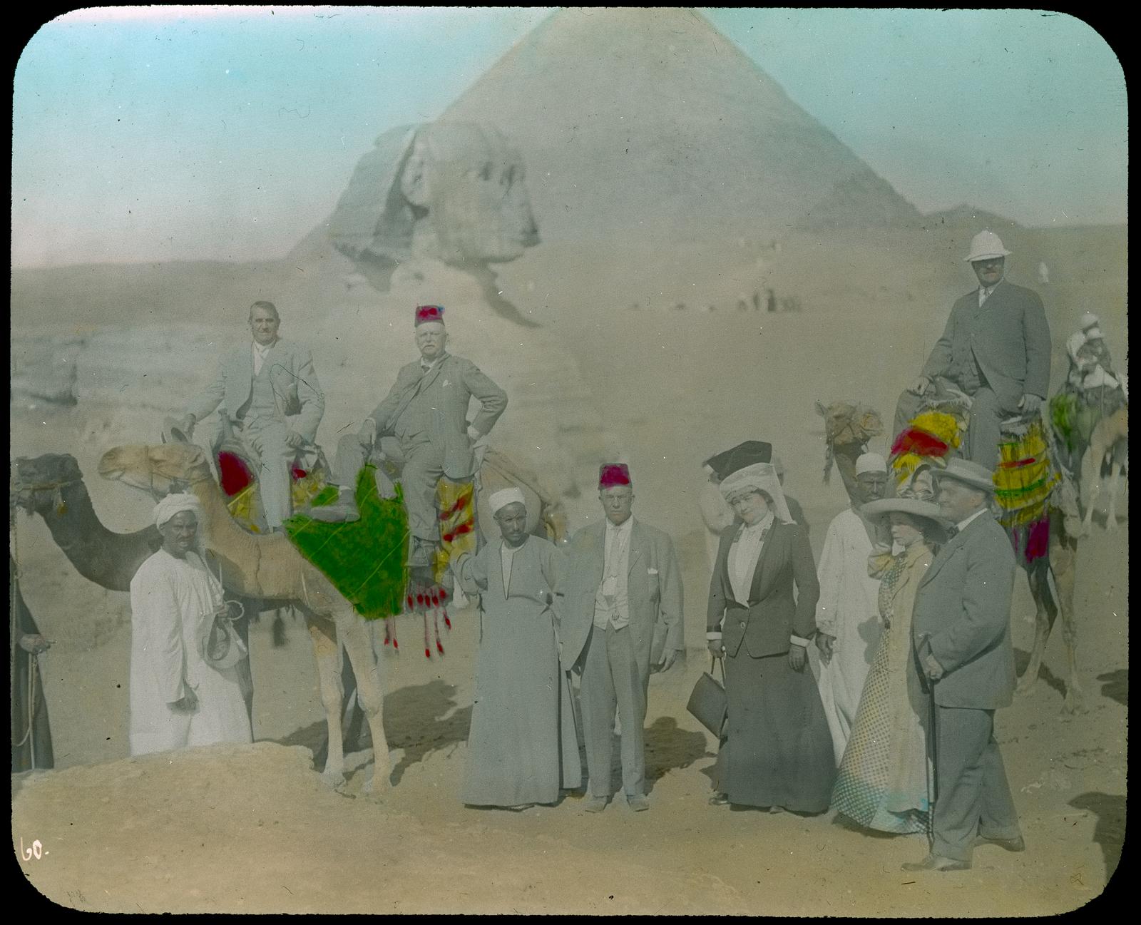 Гиза. Туристы и местные гиды с верблюдами перед Сфинксом и пирамидами