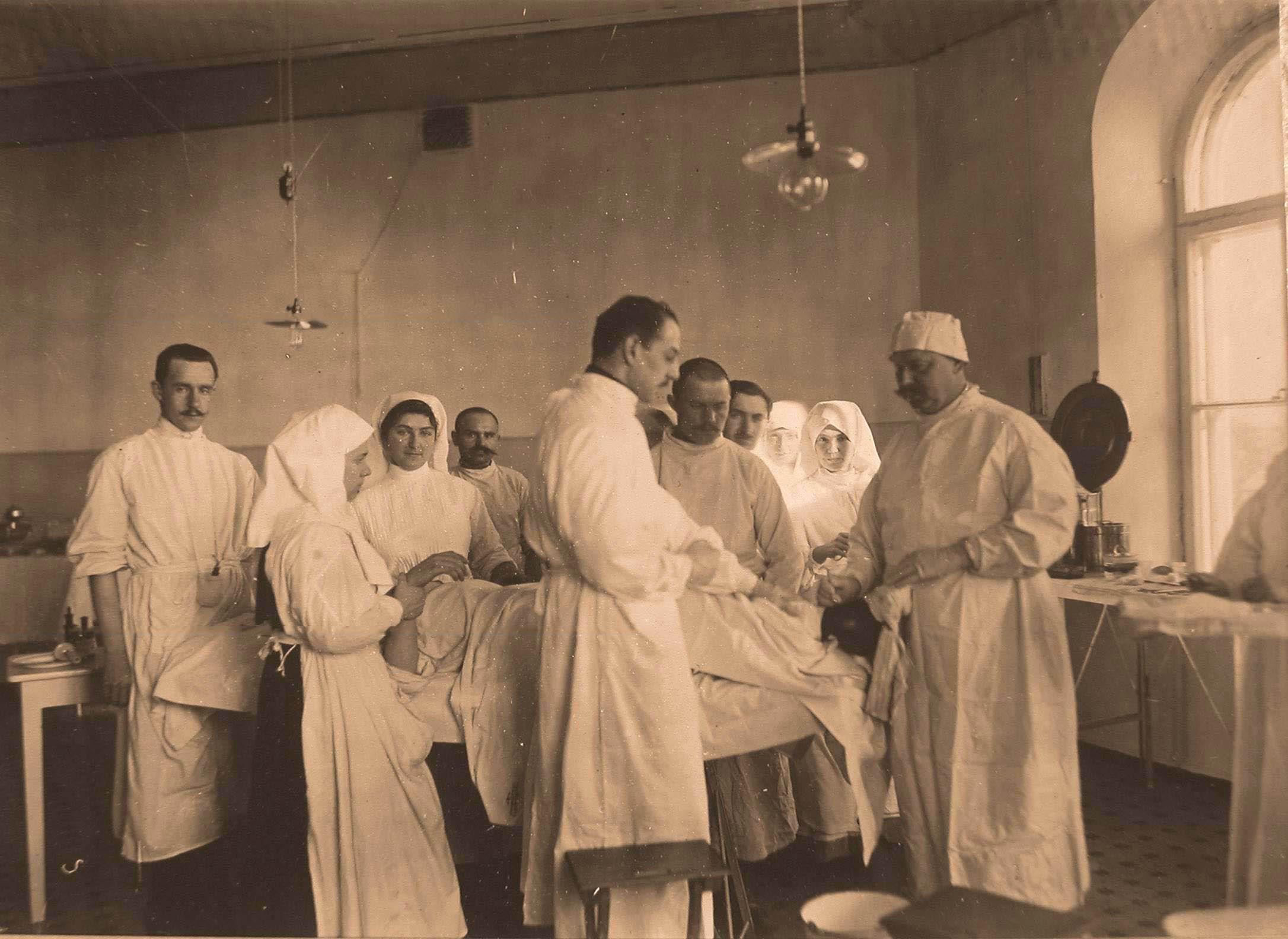 13. Группа врачей и сестёр милосердия во время проведения операции раненому в ногу; крайний справа- профессор И.Х.Дзирне
