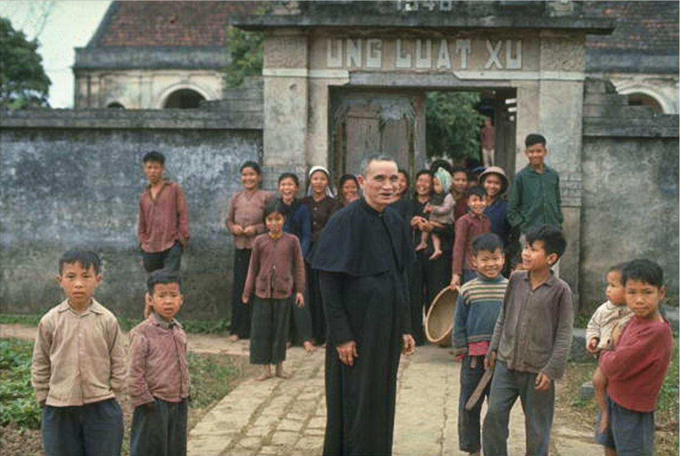 Католический священник и некоторые из его паствы у церковной ограды
