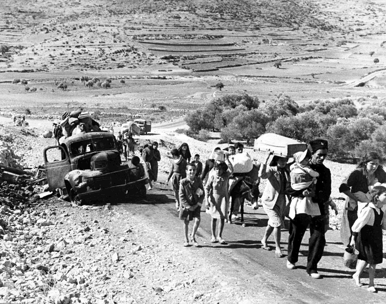 Группа арабских беженцев идет по пыльной дороге из Иерусалима в Ливан, унося свои скудные пожитки с собой, 9 ноября