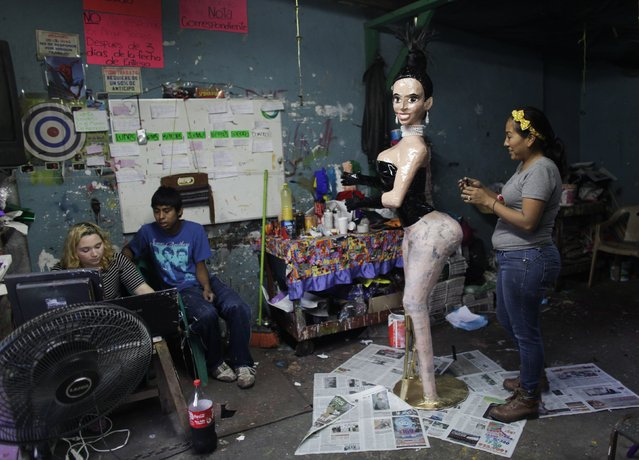 Adriana Ramirez (R) works on the outfit for a pinata depicting TV celebrity Kim Kardashian at her br