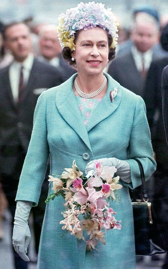 The Queen 1966 Queen Elizabeth II sporting a blue coat and floral appliqué hat while visiting the National Resistance Monument in Liege on her State Visit to Belgium..jpg