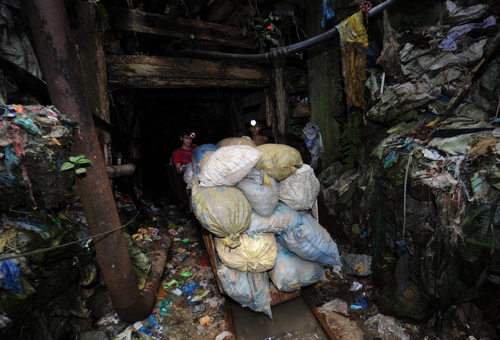 17. Копатели толкают тележку, загруженную рудой для переработки, возле шахты у горы Дивата в Миндана