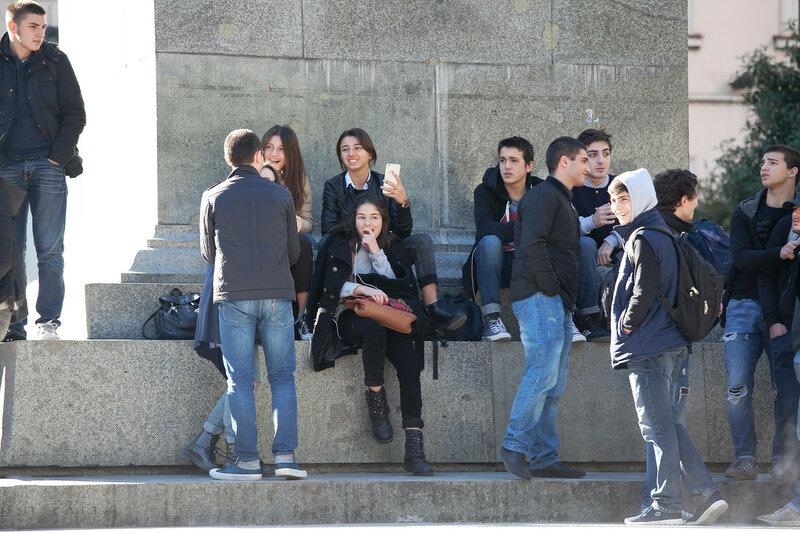 Students sitting near the monument on Rustaveli Avenue in Tbilisi, Georgia
