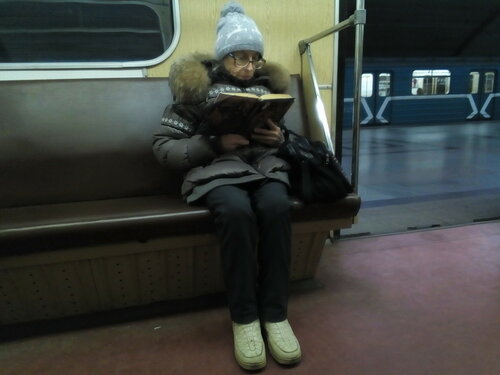 Бабушка читает книгу в метро