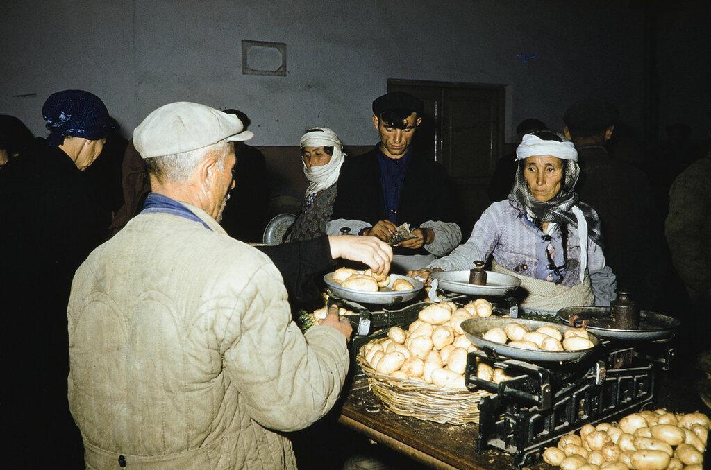 Russia, merchant selling potatoes at market
