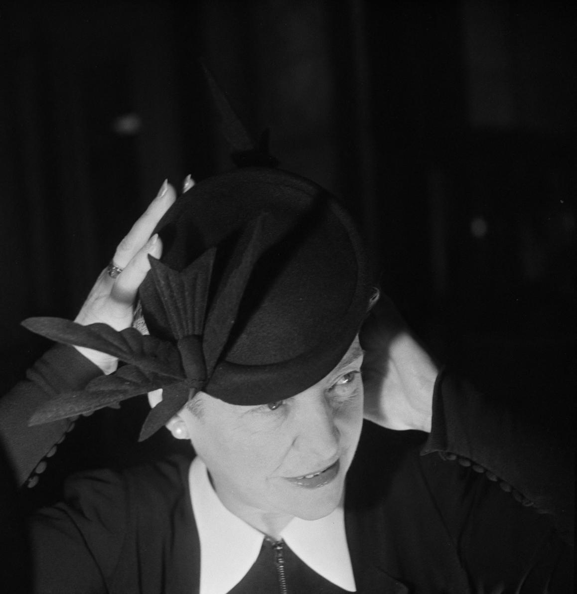 32. Женщина примеряет шляпу