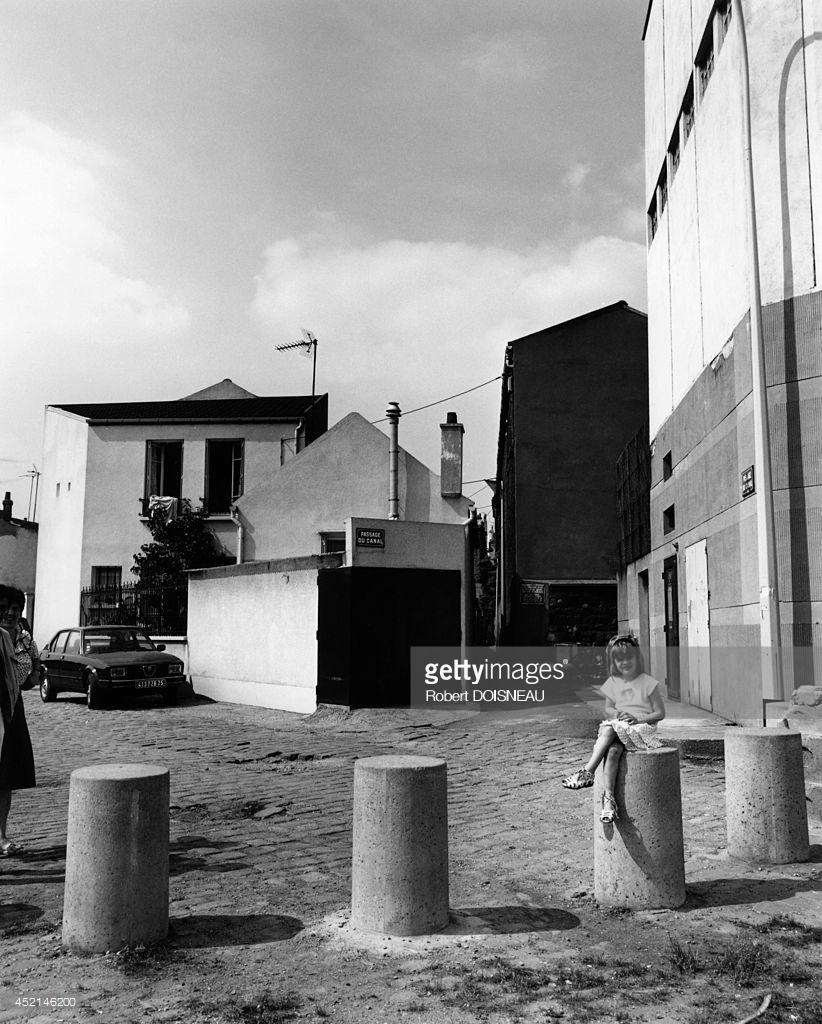 1986.  Маленькая девочка, сидящая на улице в Сен-Дени