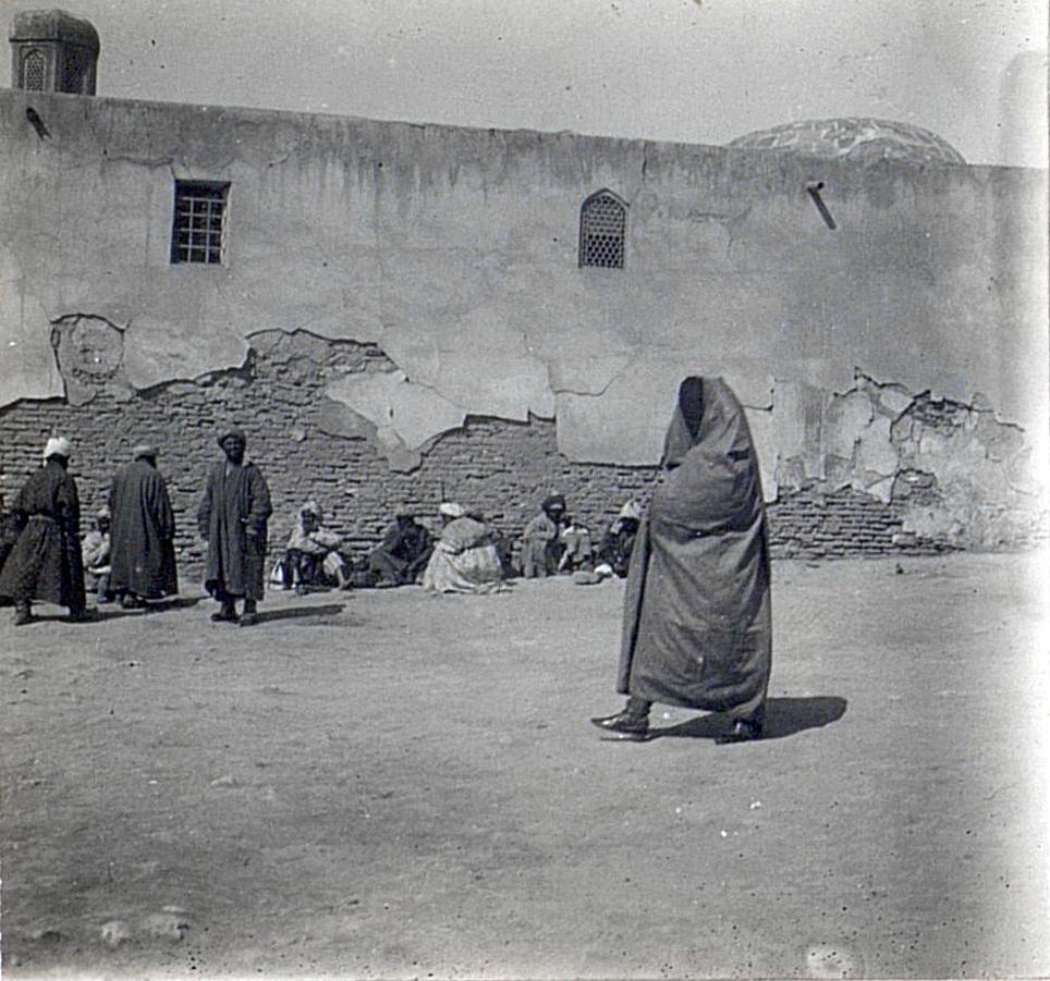 Женщина в парандже на площади Регистан у стены медресе Дорушифо