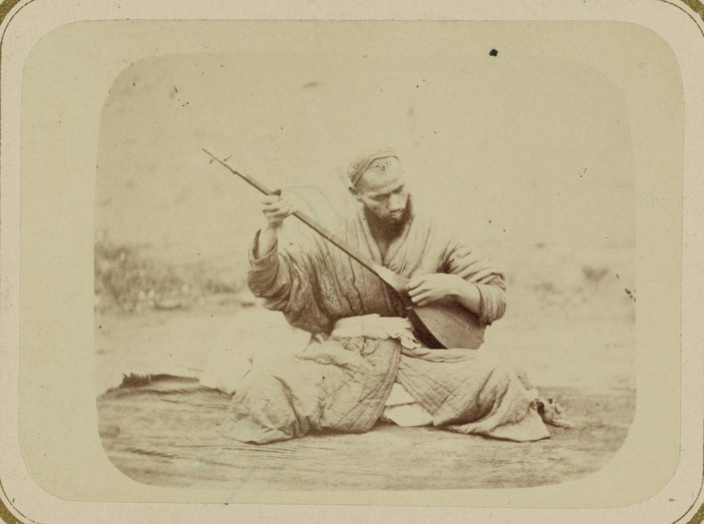 Музыкальные инструменты и музыканты. Мужчина за игрой на дутаре - лютне с ладами и длинным грифом