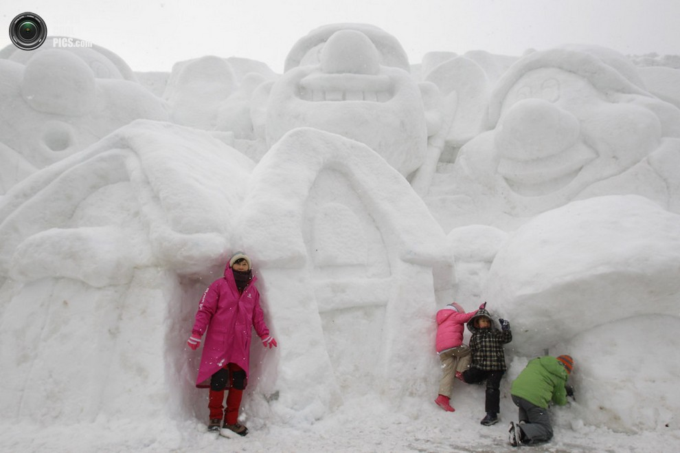 Женщина с детьми фотографируется на фоне снежных скульптур. (Chung Sung-Jun/Getty Images)